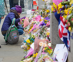 Westminster, London, March 27th 2017. A woman places a candle at the flowers attached to the fence of Parliament, yards from where PC Keith Palmer was stabbed to death by his attacker. Credit: ©Paul Davey<br /> <br /> ©Paul Davey<br /> FOR LICENCING CONTACT: Paul Davey +44 (0) 7966 016 296 paul@pauldaveycreative.co.uk