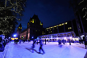 People skate on the temporary ice rink at the Natural History Museum, London. Each year around winter / Christmas time these ice rinks spring up in various locations across London. They prove incredibly popular for friends and families and draw large crowds fo people for some outdoor skating.