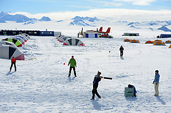 """© Licensed to London News Pictures. Union Glacier, Antarctica. RETIEF JOUBERT resident of Perth, Australia batting. Competitors from the Antarctic Ice Marathon play a game of impromptu """"Ashes"""" cricket at the Union Glacier camp, Antarctica ahead of the 2013 Antarctic Ice Marathon, which takes place  just a few hundred miles from the South Pole at the foot of the Ellsworth Mountains.. The majority of players were either Australian and English. It was declared a sporting draw. Photo credit: Mike King/LNP"""
