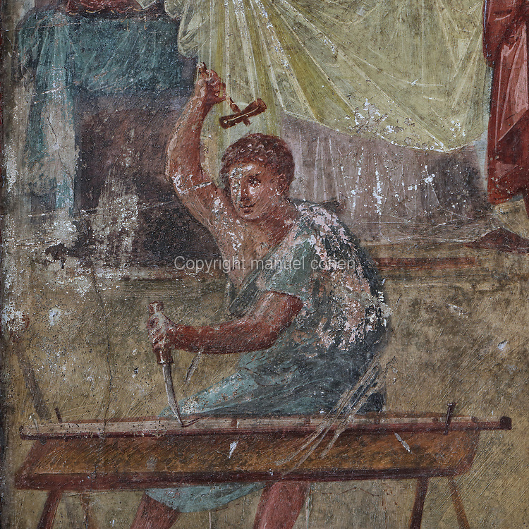 Fresco of a young apprentice at work, detail from the scene of Daedalus presenting the wooden cow to Pasiphae, in the Ixiom Room, painted after 62 AD in Pompeiian Fourth Style, in the House of the Vettii, one of the largest houses in Pompeii, in the Parco Archeologico di Pompei, or Archaeological Park of Pompeii, Campania, Italy. Pompeii was a Roman city which was buried in ash after the eruption of Vesuvius in 79 AD. The site is listed as a UNESCO World Heritage Site. Picture by Manuel Cohen