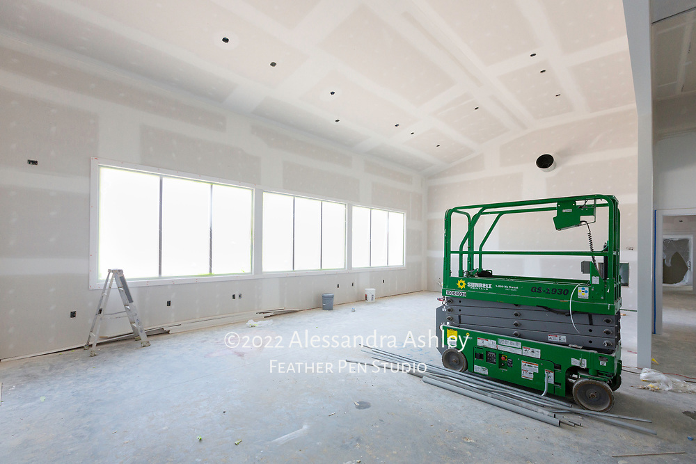 Priming in progress as painting begins at building site of new physical therapy and wellness center.