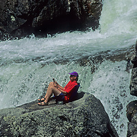 Rob Hart relaxes in a Crazy Creek chair that he invented, beside a waterfall in it's namesake river.