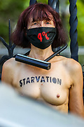 A topless Climate activist stands calm after they locked themselves against the railings of the Houses of Parliament, during an Extinction Rebellion (XR) protest, in London on Thursday, Sept. 10, 2020. Environmental nonviolent activists group Extinction Rebellion enters its 10th and final day of continuous ten days protests to disrupt political institutions throughout peaceful actions swarming central London into a standoff, demanding that central government obeys and delivers Climate Emergency bill. (VXP Photo/ Vudi Xhymshiti)