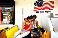 """Enjoying their day off from work, Maria Macias, 19, and her fiance William Archie, 20, wait for a ride outside of the AM PM Quick Stop. Maria says of her """"soul-mate,"""" """"He's my pride and joy, my super hero."""""""