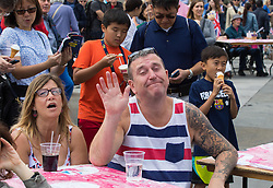 Trafalgar Square, London, June 12th 2016. Rain greets Londoners and visitors to the capital's Trafalgar Square as the Mayor hosts a Patron's Lunch in celebration of The Queen's 90th birthday. PICTURED: Dressed in red, white and blue a man relaxes with a drink.