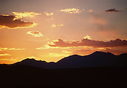 Sunset fills these clouds with orange and purple hues and creates this mountain range silhouette.