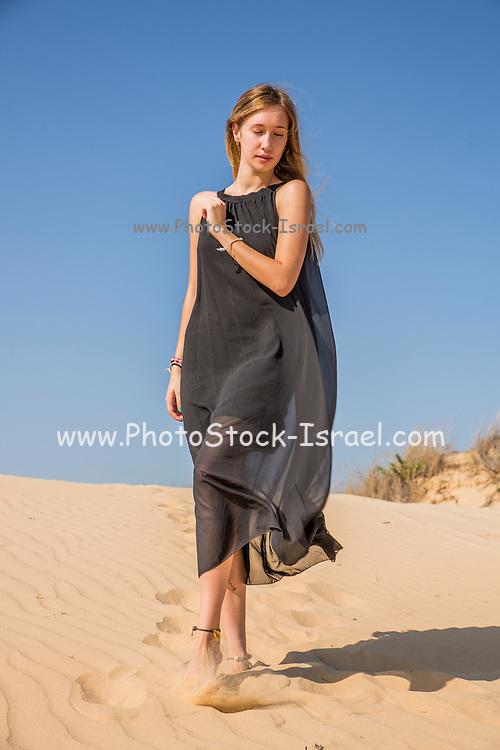 Woman in long black dress on the beach Model released