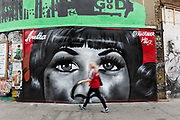 A woman walks past new street art graffiti in Shoreditch, east London, England on August 19, 2018 that pays tribute to the singer, Aretha Franklin who has died following a battle with pancreatic cancer.  The mural has been created by artist, Jules Muck in collaboration with Global Street Art.