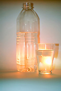 a back lit glass and bottle of refreshing mineral water with ice cubes