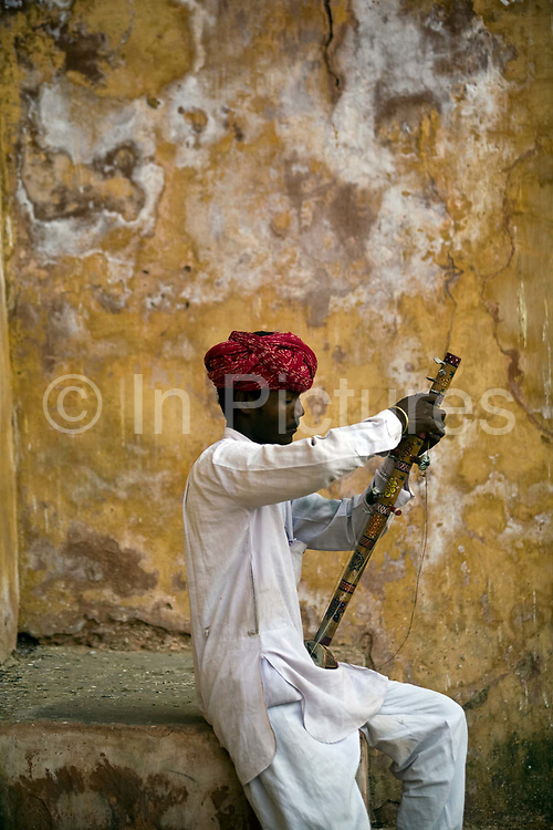 A traditional Rajasthani gypsy musician tunes his Ravanhatta (violin) inside the Amber Fort<br /> The Amer Fort, was built over the remnants of an earlier structure during the reign of Raja Man Singh, Commander in Chief of Akbar's army in 1592.The structure was expanded by his descendants, over the next 150 years