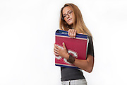 A young woman in her 20s holds an office binder on white background