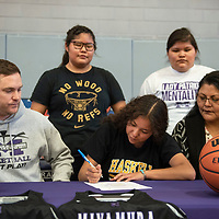Miyamura Lady Patriot Odessa Begay, center, signs a letter of intent to attend Haskell Indian Nations University and play for the Fightin' Indians women's basketball team surrounded by her coach, Josh Dupont, left, head coach of the Miyamura Lady Patriots, her sisters Socorro and Kansas Begay, and her mom Virginia Yazzie, Friday, April 12 at Miyamura High School.