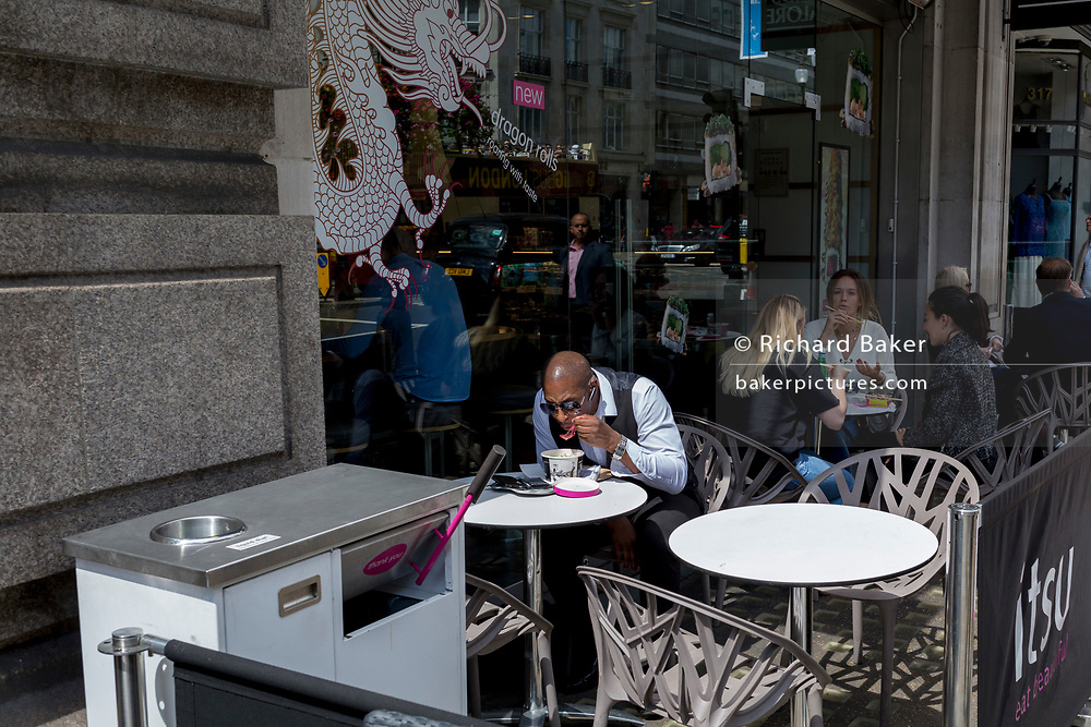 A man eats a bowl of lunchtime soup outside a branch of Itsu, on 1st August 2017, in London, England.