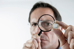 Businessman examining one euro coin with magnifying glass, Bavaria, Germany