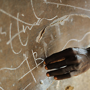 A schizophrenia patient writes on a blackboard near his home in Koidu, in eastern Sierra Leone. Switching effortlessly between his right and left hands, he covers the board in writings that are understood only by himself.