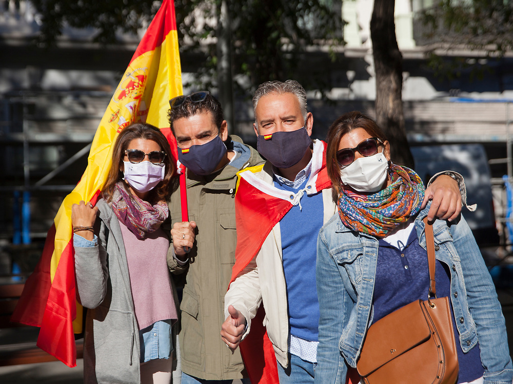 MADRID, SPAIN - OCTOBER 12: A group of friends with Spanish flags pose for the photographer on Paseo de la Castellana, on October 12, 2020 in Madrid, Spain. This year the traditional Spanish National Day military parade alongside the Paseo de la Castellana in Madrid has been canceled due to the Covid-19 pandemic and replaced by a more discreet event at the Royal Palace. (Photo by Miguel Pereira/Getty Images)