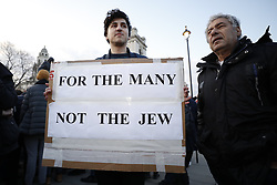 © Licensed to London News Pictures. 26/03/2018. London, UK. A protestor carries a placard  mocking Labour Leader Jeremy Corbyn's election phrase 'For the many, not the few' as members of the Jewish community, Jewish leaders and supporters hold a demonstration outside the Houses of Parliament in London against Jeremy Corbyn, who they accuse of not acting on anti-semitic behaviour in the Labour Party. Photo credit: Peter Macdiarmid/LNP