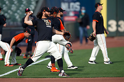 Oct 7, 2021; San Francisco, CA, USA; San Francisco Giants infielder Brandon Crawford, center, throws the ball during NLDS workouts. Mandatory Credit: D. Ross Cameron-USA TODAY Sports