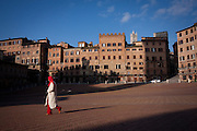 A woman walks across the shadows of Palazzo Pubblico in Piazza del Campo with the Duomo belltower in the distance, Siena, Tuscany, Italy.