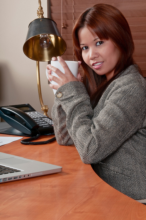 Young worker relaxing and drinking coffee in the office.