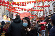 People wearing face masks for Chinese new year celebrations on Gerrard Street in Chinatown on 26th January 2020 in London, England, United Kingdom. Due to the recent coronavirus outbreak an increased number of Chinese / Asian and western people are wearing face masks in public despite NHS Englands advice that the risk of getting the illness in the UK is low. Wuhan novel coronavirus WN-CoV is a new respiratory illness that has not previously been seen in humans. Each year local Chinese community and Londoners gather on this famous area of central London which is the focus of celebrations for this, the Chinese Year of the Rat. Bright red lanterns are strung across between the buildings creating a canopy of colour.