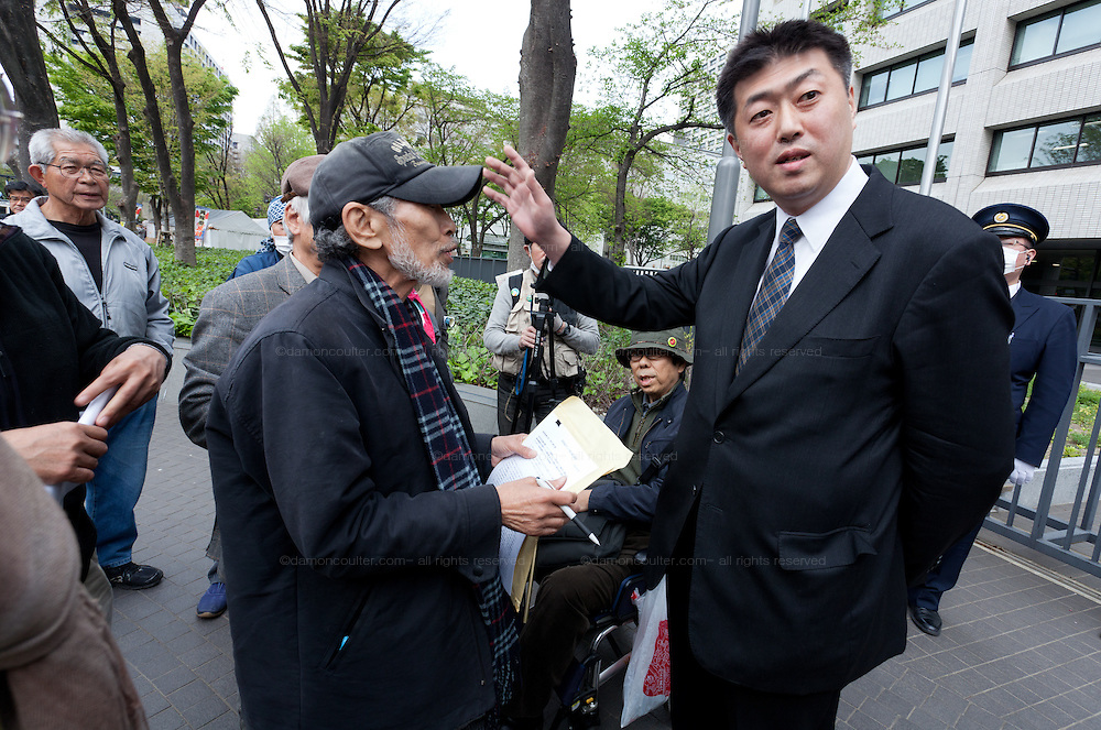 """Taro Fuchigami (in baseball cap) talks with a Ministry official outside the METI building in Kasumigaseki, Tokyo, Japan. Friday April 12th 2013. The camp has been in place since September 2011 resisting several attempts to remove it. It now faces a court order restricting access and protestors have been served with a order to pay """"rent"""" for their use of the land."""