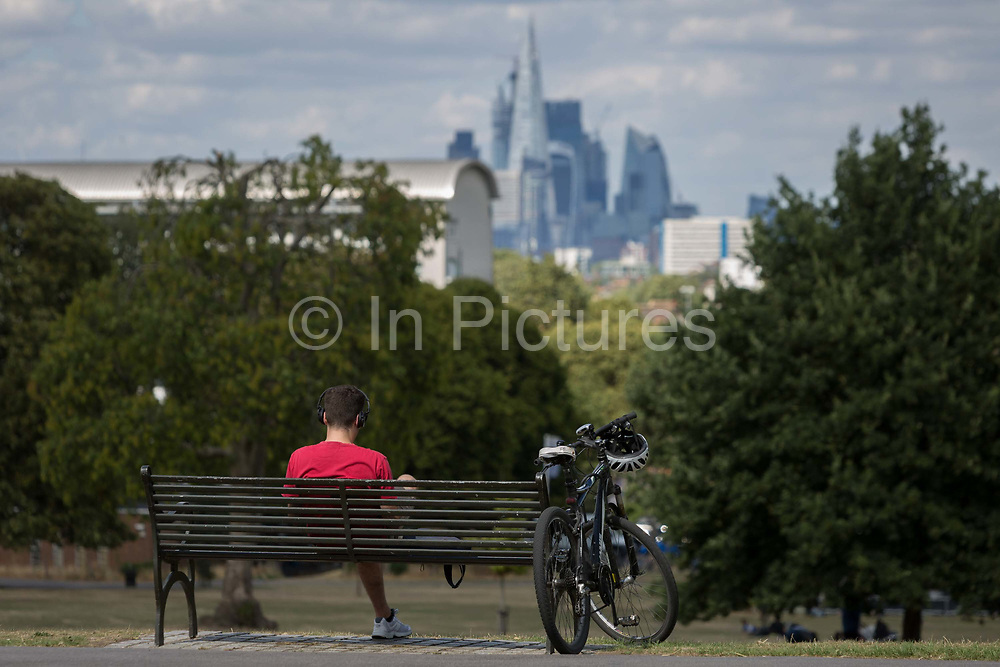 A cyclist wearing a red t-shirt sits on a park bench with the City of Londons financial skyline in the distance, in Brockwell Park, on 8th August 2018, in London, England.