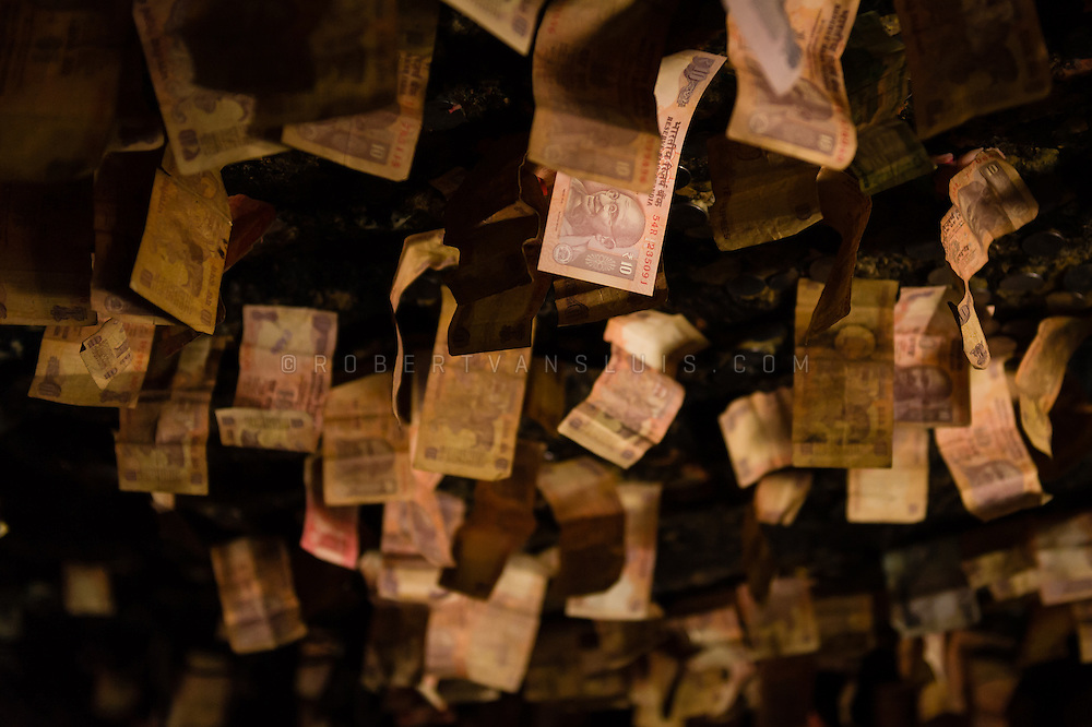 Money stuck to the ceiling of a meditation cave in Tak Tok Monastery, Ladakh, India