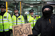 London, UK. Wednesday 19th November 2014. Student Assembly Against Austerity demonstration in protest at education spending cuts, tuition fees, and the resulting students debt. Demonstrator holds up a sign saying 'Fascist' in front of police.