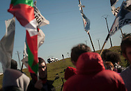 People taking part on the march,  with basque flags and banners asking the repatriation of basque prisoners, looak at some police patroling the surrounding area of the prison. CAceres (Spain). February 20, 2016. Some friends and relatives of Basque political prisoners take part on a march to Caceres penitentiary center, within the campaign of 40 marches to 40 prisons where Basque prisoners are imprisoned. These marches are to denounce the dispersal policy those prisoners suffer since more than 25 years. (Gari Garaialde / Bostok Photo)