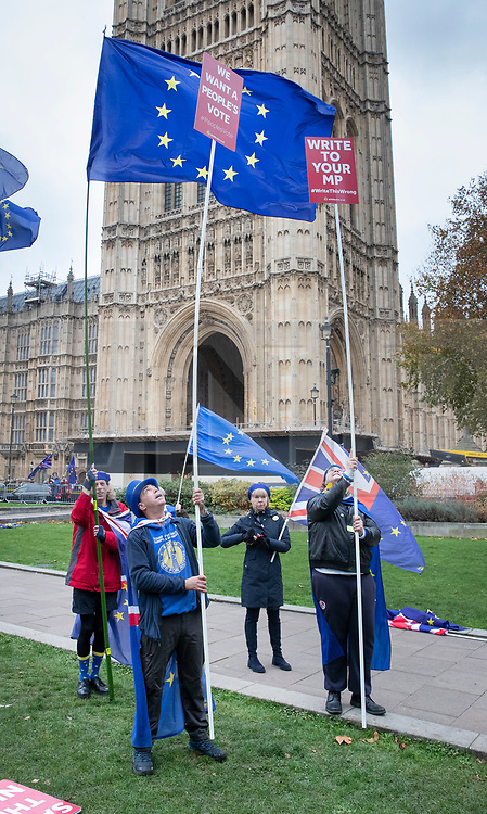 © Licensed to London News Pictures. 26/11/2018. London, UK. Anti-Brexit campaigners have placed placards and posters on extended poles after broadcasters built tall platforms to give them a clear view of Parliament. Prime Minister Theresa May will update the House of Commons later on the EU withdrawal deal agreed by the 27 member states at the weekend. Photo credit: Peter Macdiarmid/LNP
