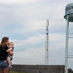 August 4, 2017 - Tangier Island, VA - Layla Park kisses her nephew near the cell phone and water tower of Tangier Island . Due to the island's diminishing surface area it is uncertain whether Tangier Island youth will grow up on the island as generations of their ancestors have done on the small, tight-knit island community of watermen and their families.<br /> <br /> Photo by Susana Raab/Institute