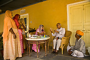 Nobleman Nahar Singhji, also known as Rao Saheb  together with his daughter-in-law distribute homeopathic medicines to the staff of the hotel they own, the Deogarh Mahal Palace, as well as women from nearby villages, they support, Deogarh, Rajasthan, India.