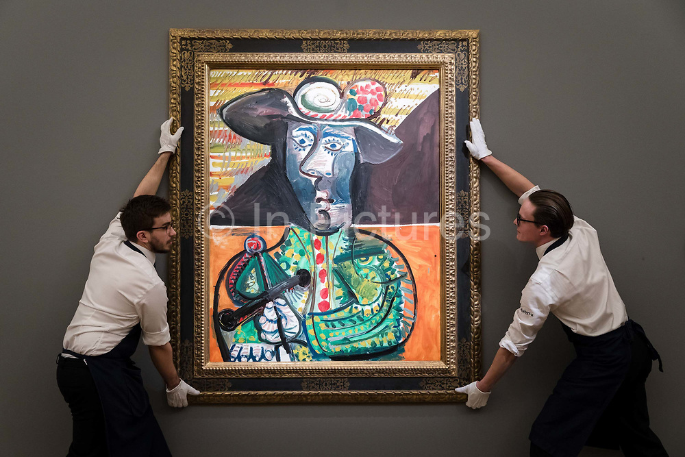 Two members of staff hold Le Matador, by Pablo Picasso, on February 22nd, 2018 at the preview for Sothebys upcoming Impressionist, Modern and Surrealist Art auction at Sothebys in New Bond Street, London, England.