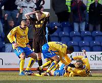 Photo. Glyn Thomas.<br /> Mansfield Town v Hull City.<br /> Nationwide League Division 3.<br /> Field Mill, Mansfield. 06/03/2004.<br /> Mansfield Town's Laurent D'Jeffo is mobbed by teammates after scoring his side's winning goal, while Hull's Richard Hinds can only hold his head in his hands.