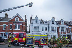 © Licensed to London News Pictures. 07/12/2020. London, UK. An aerial appliance towers over the flat as fire fighters work on the ground. Ten fire engines and around 70 firefighters responded a flat fire on Montserrat Road in Putney. Firefighters, using breathing apparatus rescued a man via an internal staircase from a second floor flat in a mid-terrace house of three floors. The man was treated for smoke inhalation by London Ambulance Service crews and taken to hospital. Photo credit: Peter Manning/LNP