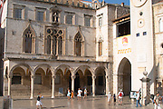 the arched porch and facade of the Sponza palace on the Luza Lodge Loggia Square on the Pred Dvorom street. Tourist walking past Dubrovnik, old city. Dalmatian Coast, Croatia, Europe.