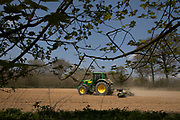 Farmer in his John Deere 7530 agricultural tractor with ring roller breaking up large clumps of soil in a field at Ivy Hatch, England, United Kingdom. This area of Kent is an agricultural area known as The Garden of England.