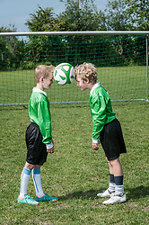 Two young soccer players learning ball control