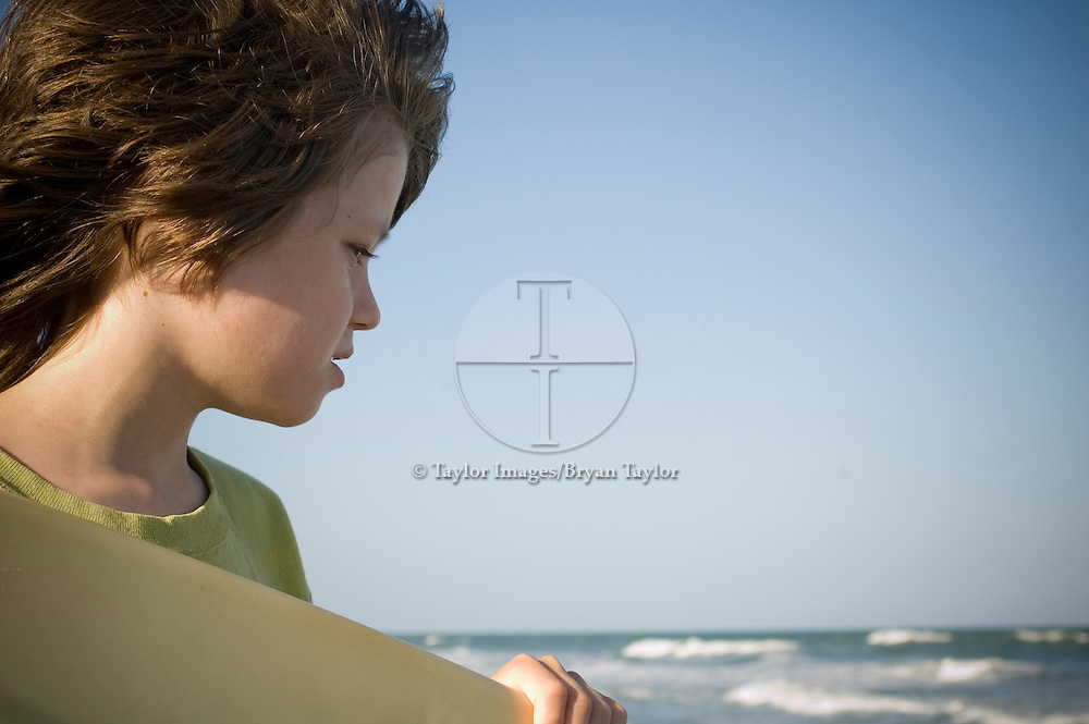 A young boy surveys the summer waves and surf with his surfboard on the beach in Myrtle Beach, South Carolina.