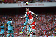 Laurent Koscielny of Arsenal heads the ball over Diafra Sakho of West Ham United. Barclays Premier League, Arsenal v West Ham Utd at the Emirates Stadium in London on Sunday 9th August 2015.<br /> pic by John Patrick Fletcher, Andrew Orchard sports photography.