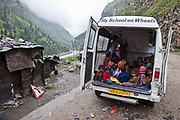A lesson for the migrant worker children run from the education bus next to a road in the Himalayas, India.  The migrant community is given education and information support by the Pragya organization who have a project helping in high altitude areas across the Himalayas.