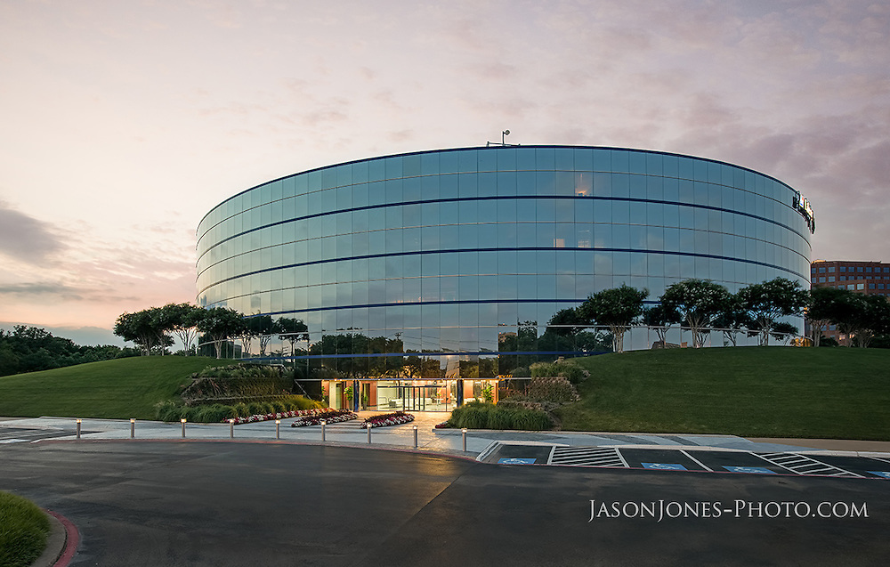 Round multi story office building at dusk, from front elevation exterior view for property management company. Inspiration for investment portfolio, auction, liquidation or financial report images and photography