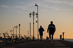 © Licensed to London News Pictures. 30/10/2017. Southsea, UK.  Two men jogging along Southsea promenade as dawn breaks on a chilly autumn morning, 30th October 2017.  Photo credit: Rob Arnold/LNP