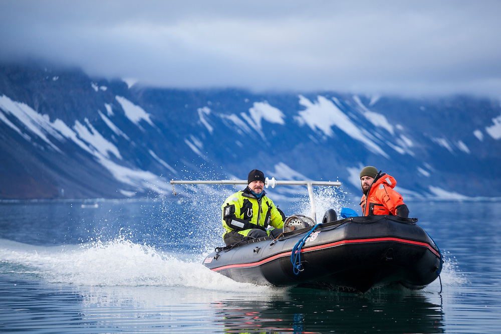 Oceanographer Waldemar Walczowski and station cook Dominik Petelski cross Hornsund in a motorboat on a field expedition to Samarinbreen glacier, Svalbard.