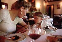 August 1997, Burgundy, France --- Annemiek Franken-Determann sits with her son, Tunui, in a restaurant. --- Image by © Owen Franken/CORBIS
