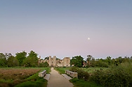 Full moon rising above the ruins of Cowdray Castle. Midhurst, West Sussex.<br /> Picture date: Wednesday May 6, 2020.<br /> Photograph by Christopher Ison ©<br /> 07544044177<br /> chris@christopherison.com<br /> www.christopherison.com<br /> <br /> IMPORTANT NOTE REGARDING IMAGE LICENCING FOR THIS PHOTOGRAPH: This image is sold as an open edition print by the artist. No secondary sales or reproduction permitted unless expressly agreed in writing by the photographer.