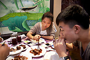 Young customers in the main dining room. Quanjude roast duck restaurant in Wangfujing, Beijing. This is a Chinese restaurant known for its trademark Peking Roast Duck and is known for being the best roast duck restaurant in China. Quanjude was established in 1864 during the Qing Dynasty under the reign of the Tongzhi Emperor. Although Peking Duck can trace its history many centuries back, Quanjude's heritage of roast duck preparation - using open ovens and non-smoky hardwood fuel such as Chinese date, peach, or pear to add a subtle fruity flavor with a golden crisp to the skin, was originally reserved for the imperial families.