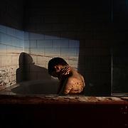 Oliver with slide of Salar de Uyuni projected onto the bathroom tiles.