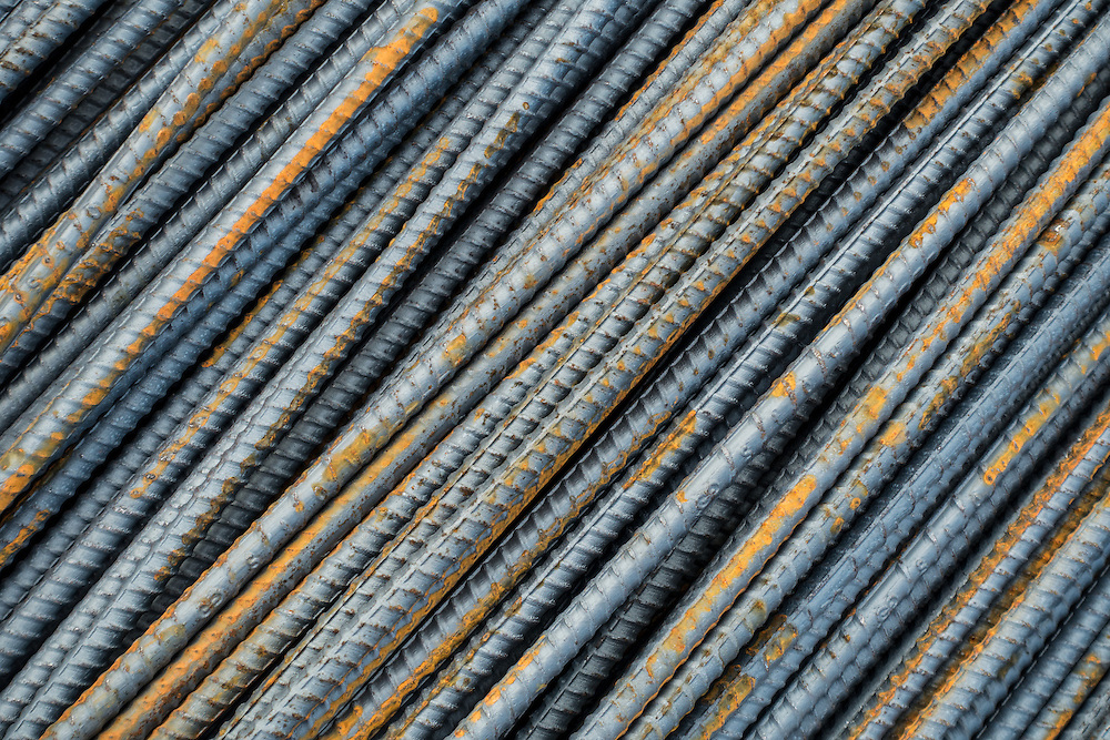 Rusting metal rebar steel grey rods are lying in a parallel pattern, forming an interesting abstract image.